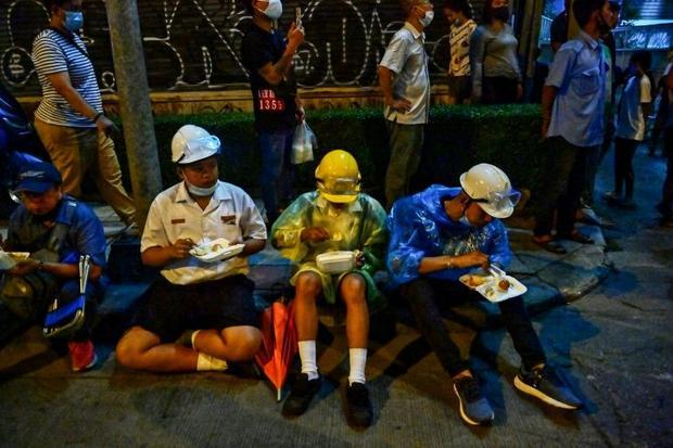 This picture taken on October 21  2020 shows pro-democracy protesters eating meals from street food ...
