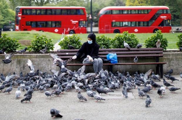 A woman wearing a face mask and gloves feeds pigeons in an almost deserted Marble Arch in London