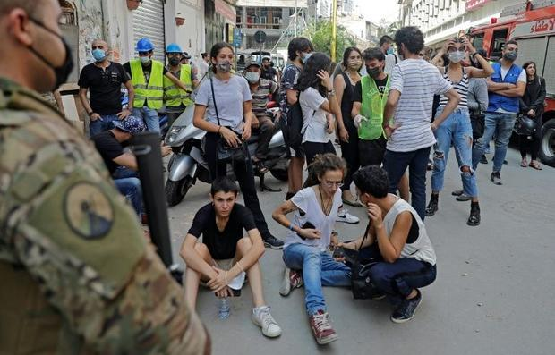 Bystanders gather as rescue workers try to reach a possible survivor of the August 4 mega-blast that...