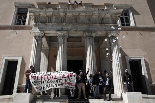 A group of anti-establishment protesters hold a banner on April 1  2015 outside the Greek Parliament...