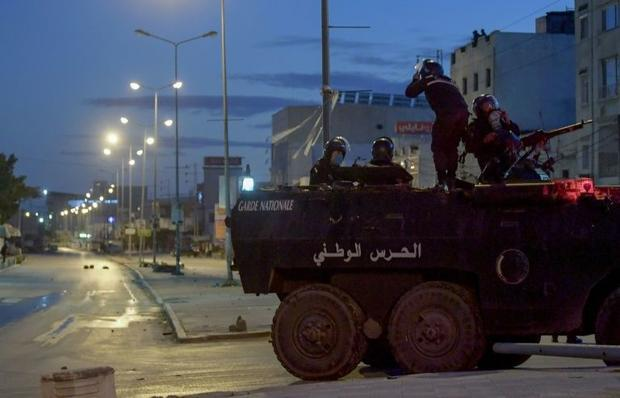 Tunisian National Guard troops on an armoured vehicle  stationed on a street amid clashes with demon...