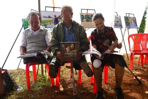 Vietnamese landmine victims Phan Van Ty (L)  Truong Uu (C) and Hoang Thi Luu (R) read books in Quang...