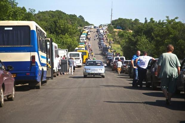 People queue at an Ukrainian checkpoint near Artemivsk on June 11  2015  to leave the territory cont...