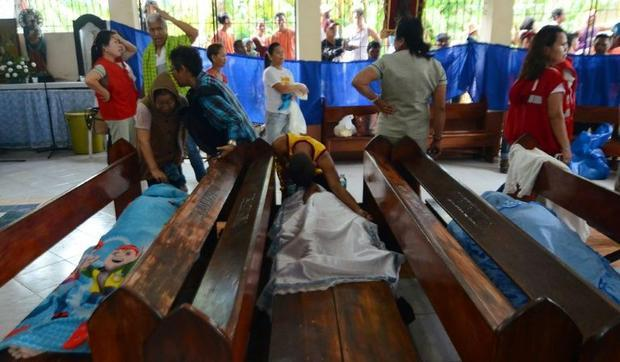 People weep next to the bodies of victims of a landslide in Naga City  on the popular tourist island...