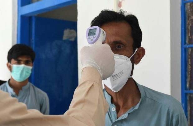 A doctor checks the body temperature of a man returning from Iran at a quarantine zone to test for t...