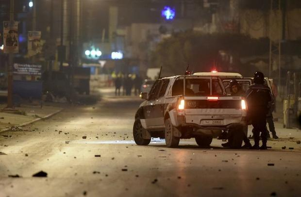 Tunisian police block a road in the working-class district of  Ettadhamen on the edge of Tunis amid ...