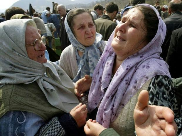 Bosnian women weep at the grave of a victim of the Srebrenica massacre at a memorial cemetery in Pot...