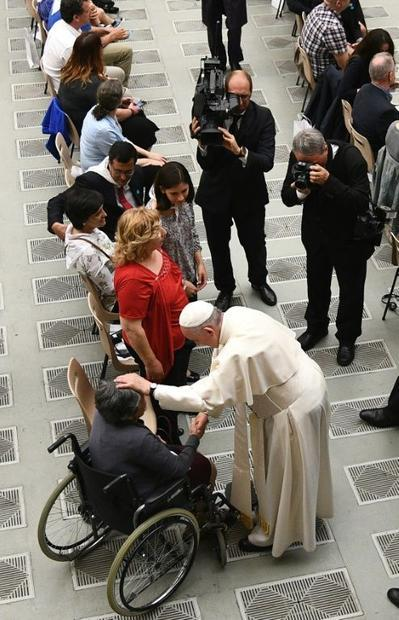 As Pope Francis embraced sufferers of Huntington's disease who had travelled to the Vatican on ...