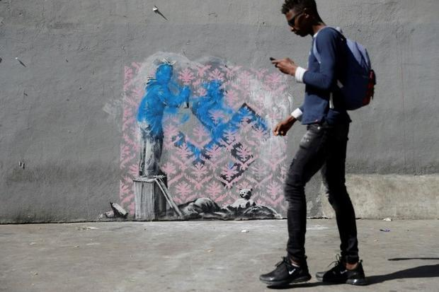 Banksy's work of a girl painting over a swastika was damaged shortly after it appeared near a m...