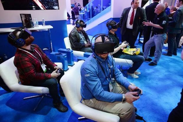 Attendees wear Oculus Rift HD virtual reality head-mounted displays as they play EVE: Valkyrie  a mu...
