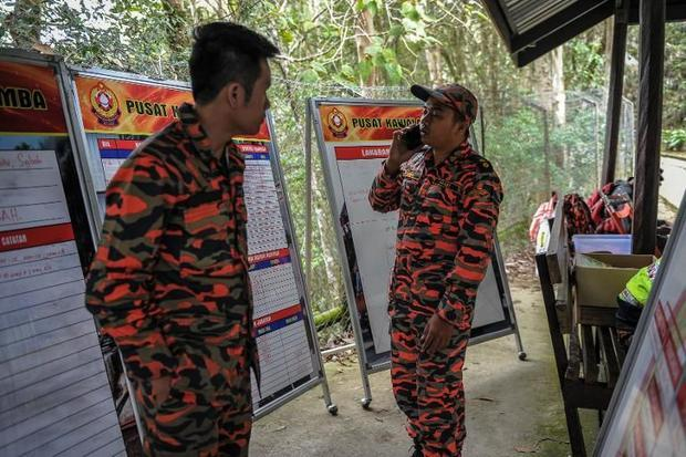 A member of a Malaysian rescue team talks with his mobile phone at the Timpohon gate checkpoint as t...