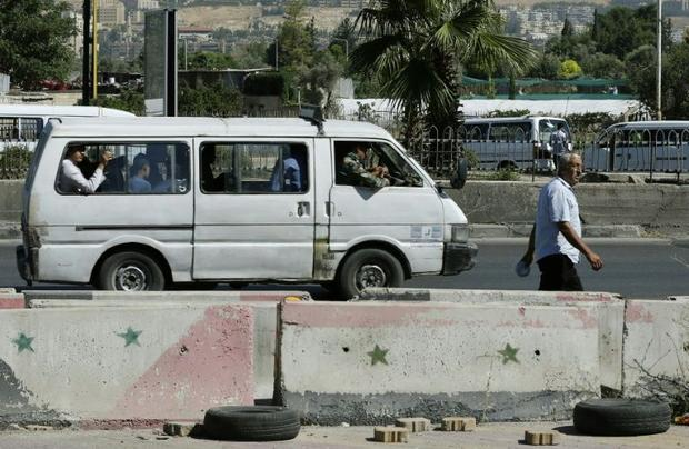 Syrians walk and drive past cement blocks on the side of the road on July 10  2018 after a security ...