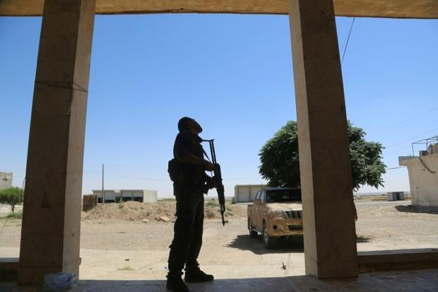 A member of the Syrian Democratic Forces scans the sky in Raqa's Al-Meshleb neighbourhood on Ju...