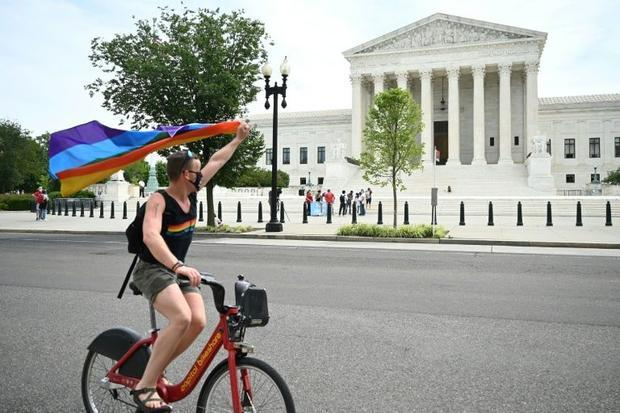 A man waves a rainbow flag as he rides by the US Supreme Court in Washington