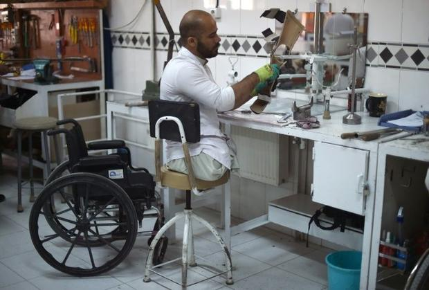 An Afghan orthopaedic technician makes artificial limbs in a workshop at the International Committee...