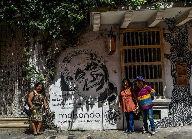 Tourists pose for a snapshot in front of a mural painting depicting the late Colombian writer and No...